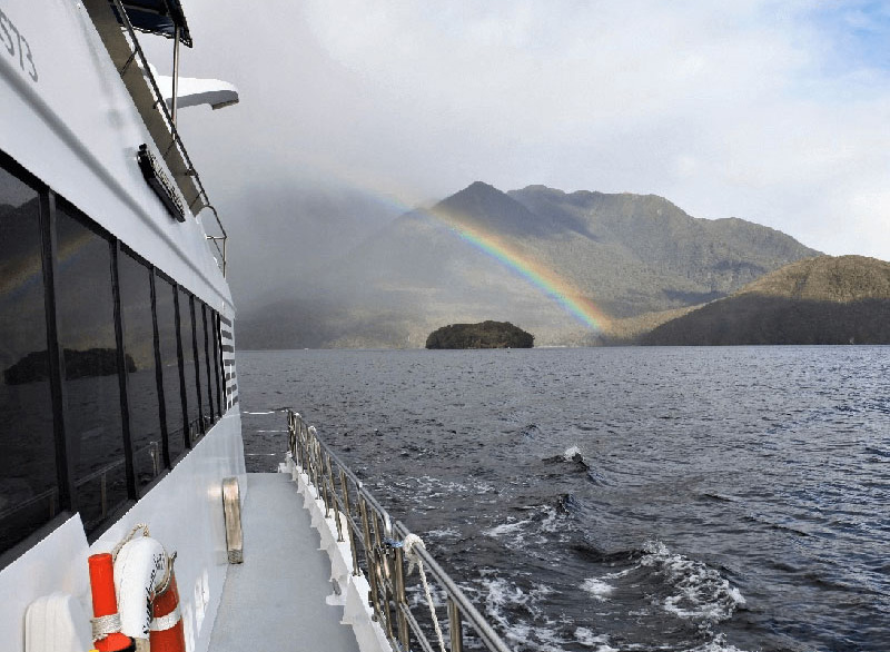 Looking back towards the aft of the Southern Secret towards a rainbow in the distance across the Fiord.