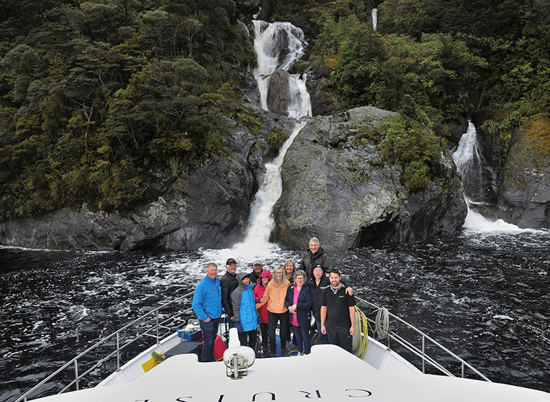 Guests gathered on the bow of the Southern Secret posing for a photo in front of a waterfall.