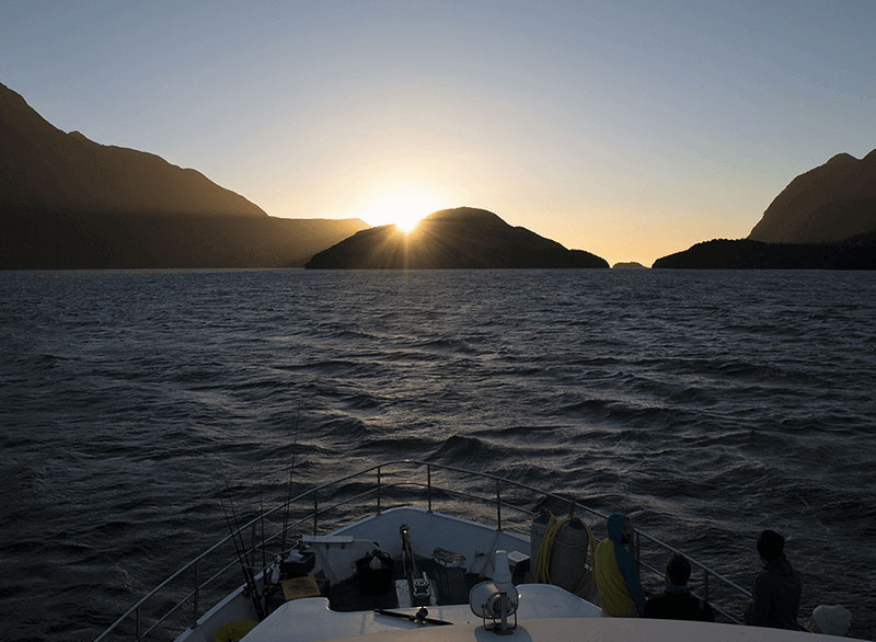 Looking over the bow of the Southern Secret out towards the setting sun on the horizon.