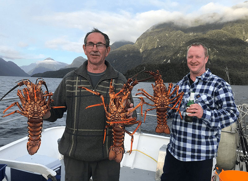 Two males on the bow of the Southern Secret holding large red rock lobsters.