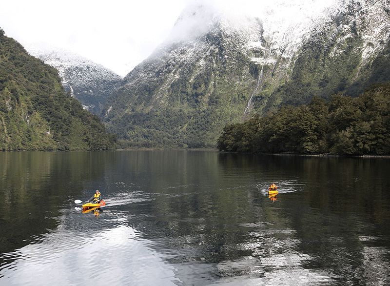Two kayakers on very calm waters of the Fiord, with snowy mountains rising up from the waters behind them.