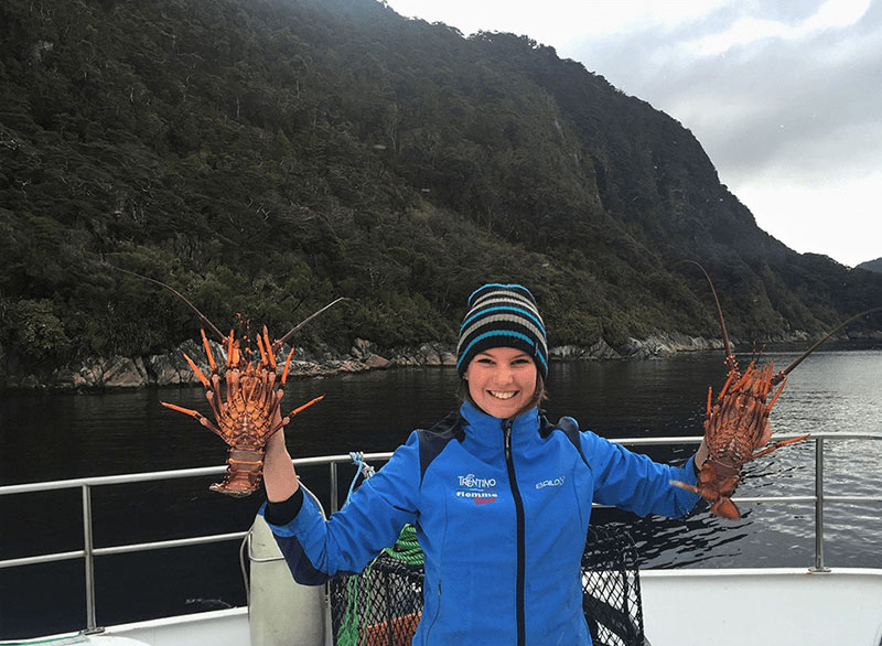 Female wearing a blue jacket  proudly raising up a red rock lobster in each hand.