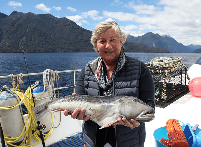 A woman proudly holding a Blue cod that she has caught onboard the Southern Secret