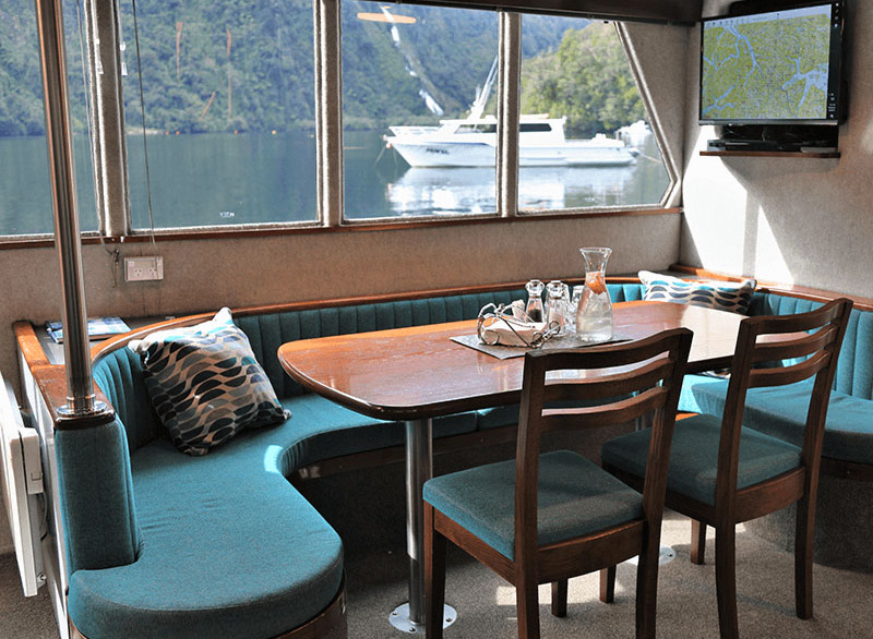 Cosy dining area onboard the Southern secret with an oak table and powder blue coloured chairs.