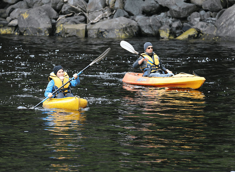 A male and female paddling yellow kayaks with the rocky shore behind them