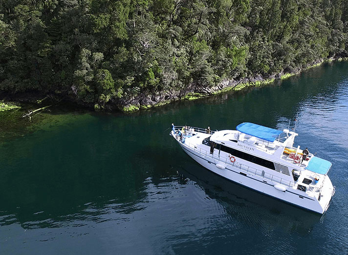 Aerial view of the Southern Secret close to shore edge on sparkling clear waters.