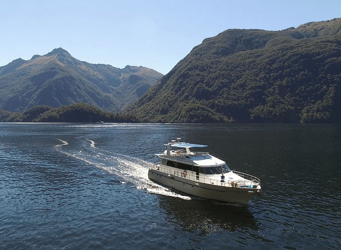 The M V Southern Secret cruising along the fiord on calm waters.