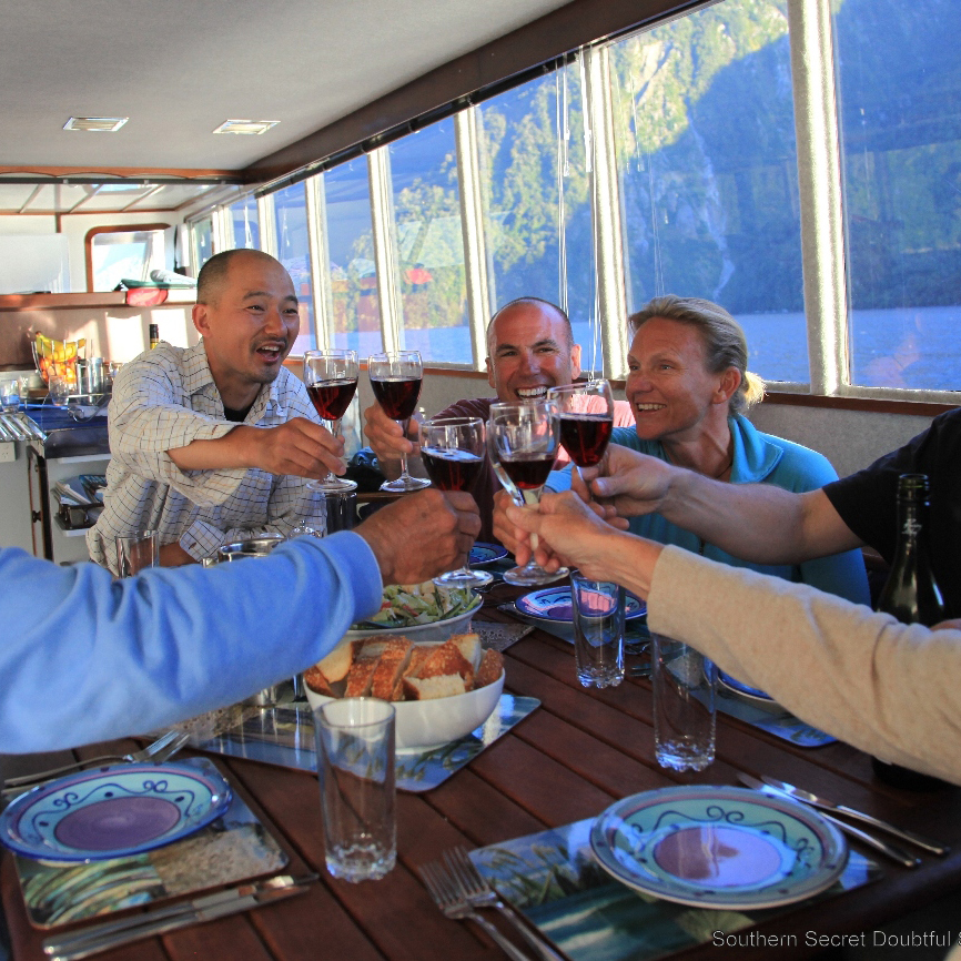 A group of six guests gathered around the dining table of the Southern Secret making a toast together with red wine.