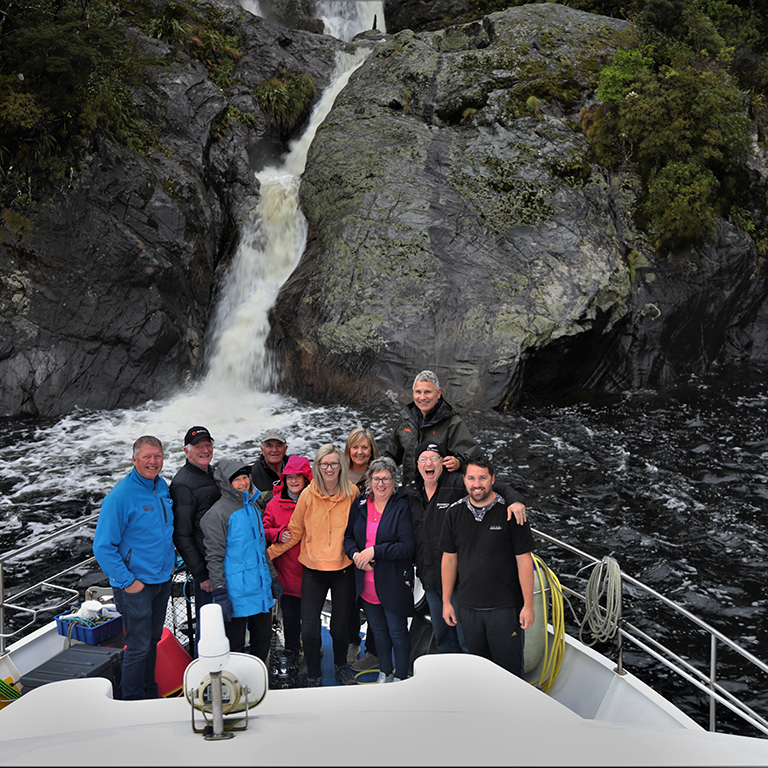 Tour group gathered on the bow of the Southern Secret smiling for the camera with waterfall in the background.