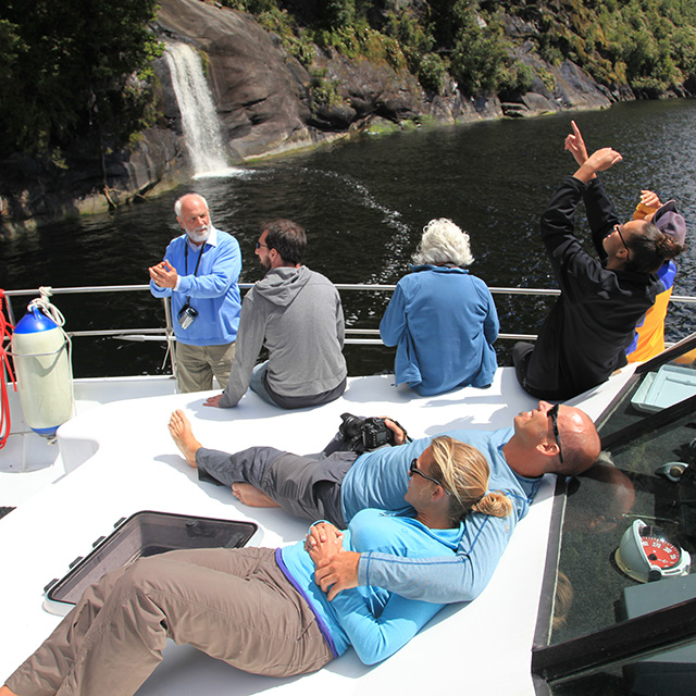 Guests relaxing on the bow of the Southern Secret and looking high up to one of the many waterfalls of Doubtful Sound.
