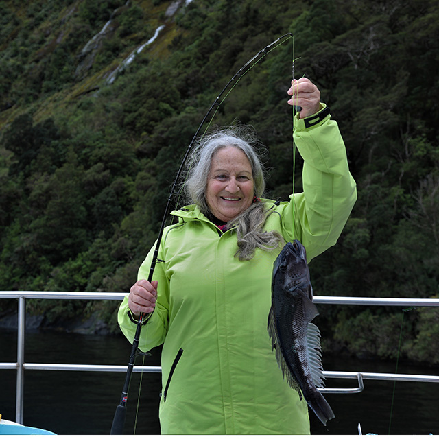 Woman in a green jacket proudly holding a fishing rod with a Blue Cod attached that she has caught.